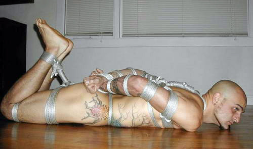 muscular man with tattoos is hogtied in rope