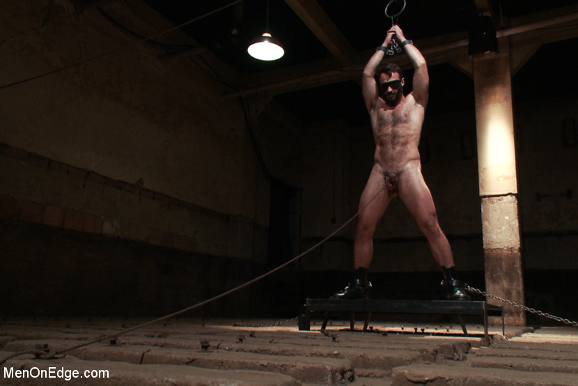 In leather, he's tied up to a pillar and blindfolded. With a hard cock, his nipples are worked over and they edge him until he curses in French. With his arms up, he gets flogged hard, then they dildo fuck his red ass.