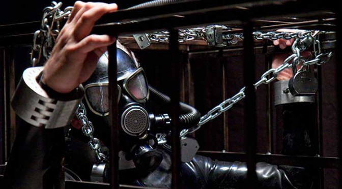 Chained inside a cage wearing a gas mask