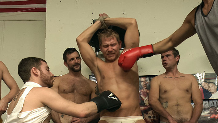 Big-cocked Alex Adams gets punished by a group of horny men at a boxing gym