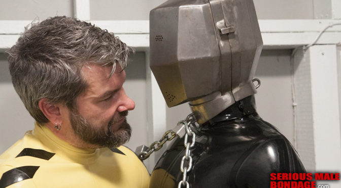 Video: A rubber gimp gets initiated in a metal head cage