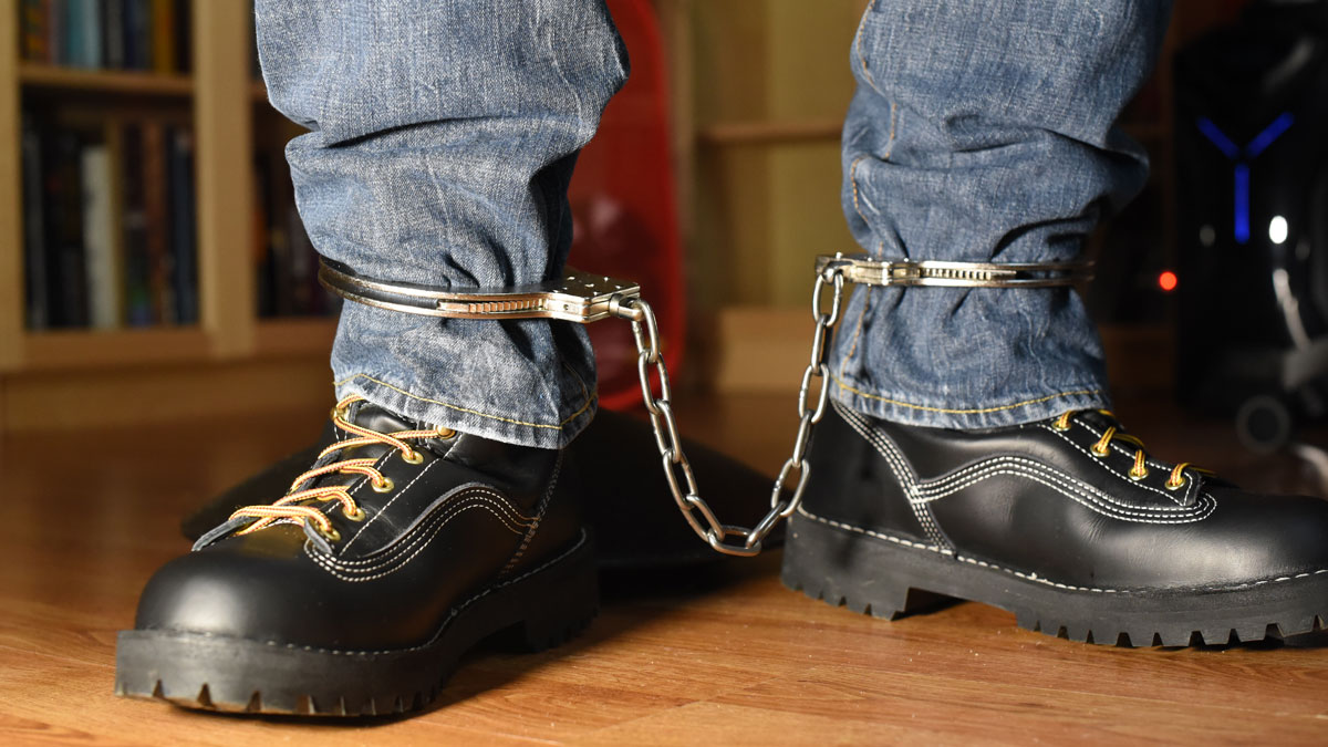 Sneaker Boy locked in customized ankle cuffs