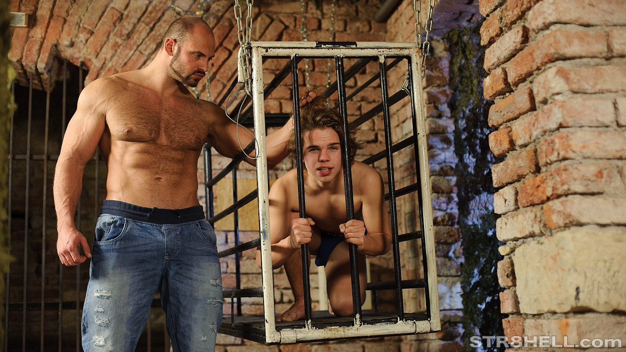 Karel is gagged and shackled in a cage