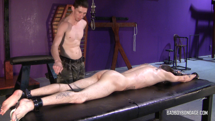 Master takes the wax off with a whip before fucking the captive's throat with his hard cock