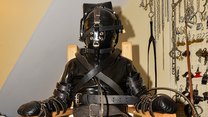 Strict chair bondage in heavy restraint gear