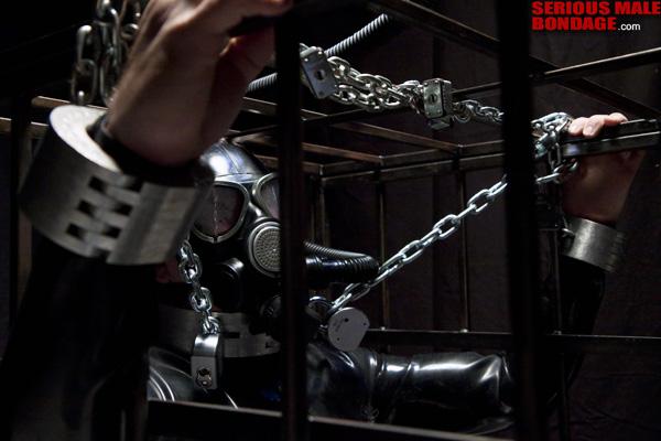 male bondage in heavy restraint gear
