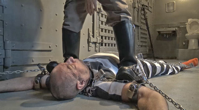 Bind is chained to the floor of the cellblock