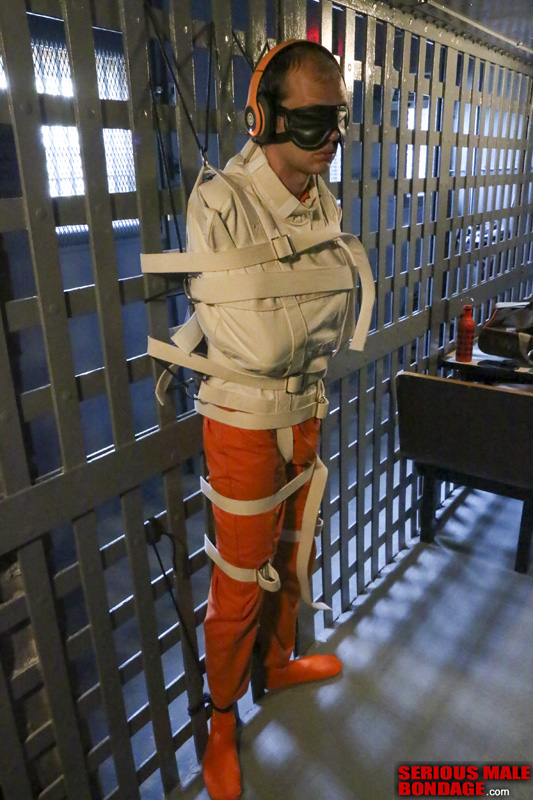 Straitjacketed to the bars of a cell